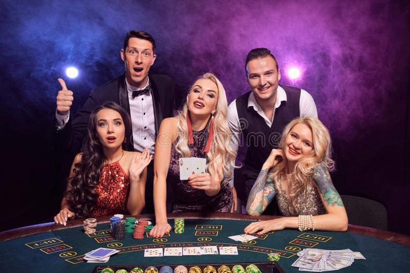 Gruppen av unga förmögna vänner spelar poker på en kasino royaltyfri foto