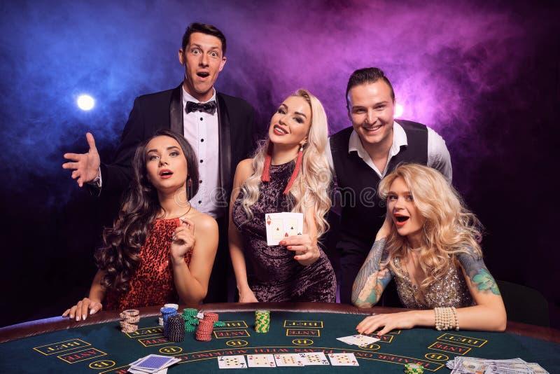 Gruppen av unga förmögna vänner spelar poker på en kasino royaltyfria foton