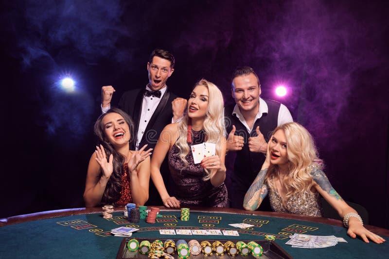 Gruppen av unga förmögna vänner spelar poker på en kasino arkivbild