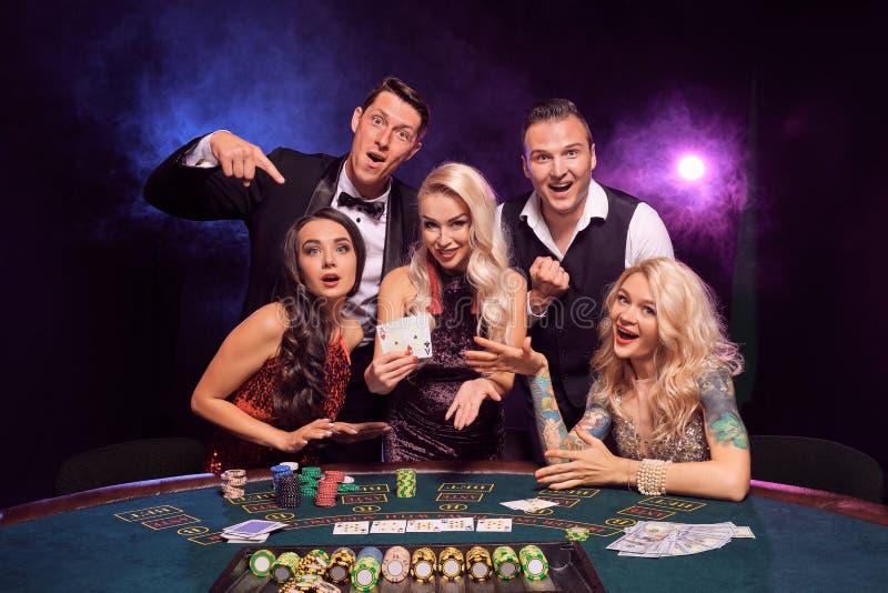 Gruppen av unga förmögna vänner spelar poker på en kasino royaltyfria bilder