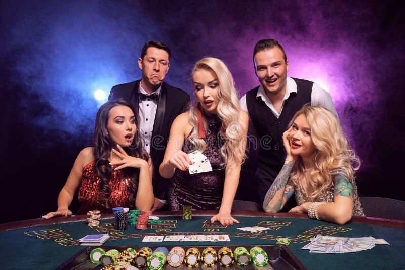 Gruppen av unga förmögna vänner spelar poker på en kasino royaltyfri fotografi