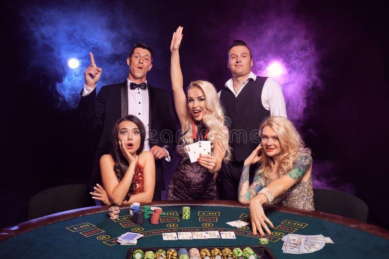 Gruppen av unga förmögna vänner spelar poker på en kasino arkivbilder