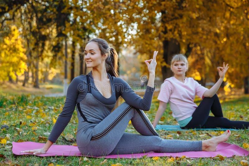 Gruppen av unga kvinnor som gör yogaövningar i höststaden, parkerar Vård- livsstilbegrepp arkivbild