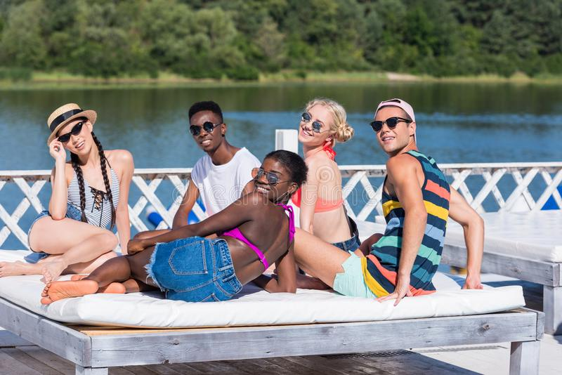 Gruppen av unga multietniska vänner vilar på poolsiden under semester arkivbild