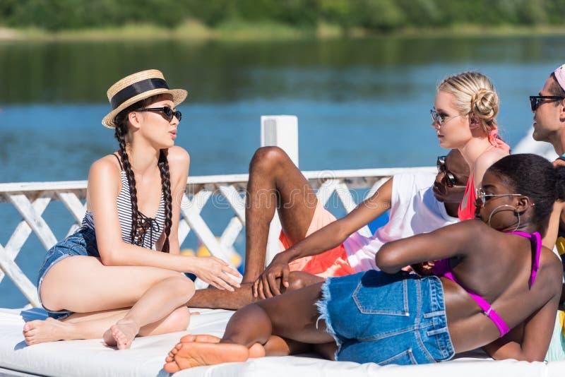 Gruppen av unga multietniska vänner vilar på poolsiden under semester royaltyfria foton
