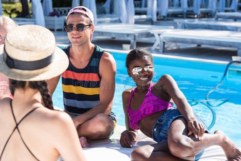 Gruppen av unga multietniska vänner vilar på poolsiden under semester arkivfoton