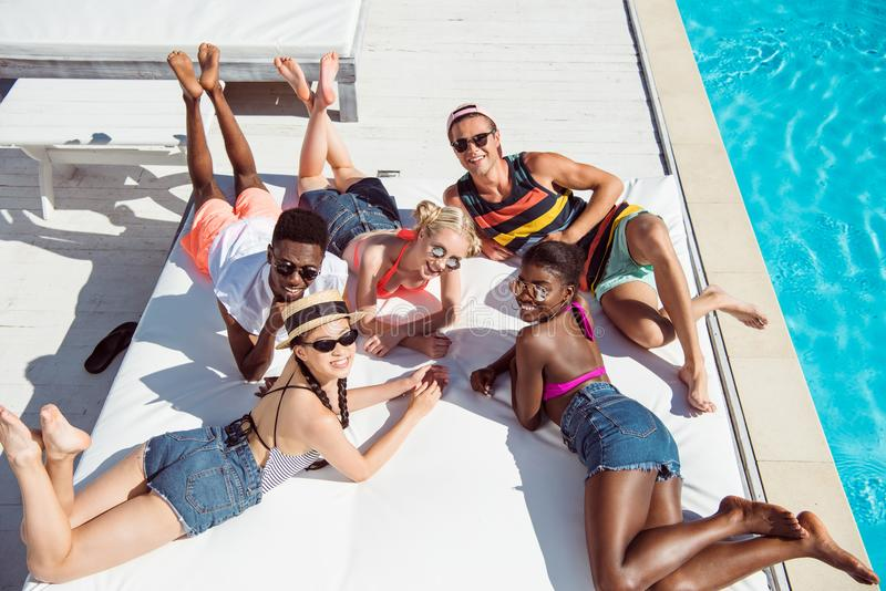 Gruppen av unga multietniska vänner vilar på poolsiden under semester arkivfoto