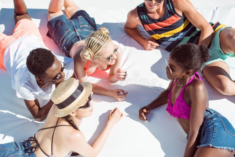 Gruppen av unga multietniska vänner vilar på poolsiden under semester royaltyfri fotografi