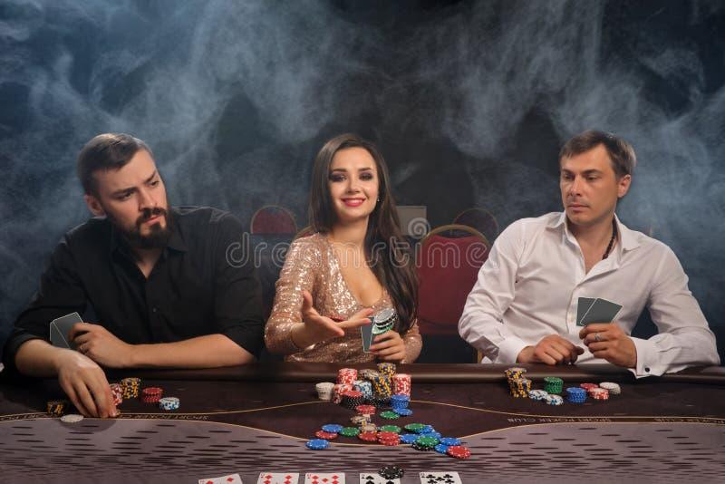 Gruppen av unga rika vänner spelar poker i kasino royaltyfri foto