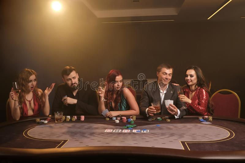 Gruppen av unga rika vänner spelar poker i kasino royaltyfri bild