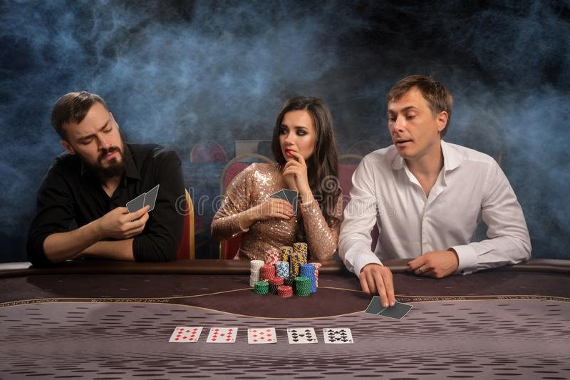 Gruppen av unga rika vänner spelar poker i kasino arkivbild