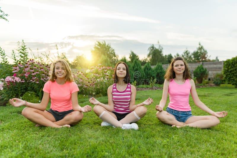Gruppen av unga tonårs- flickor övar yoga, mediterar, sitter i en lotusblommaposition på gräset nära huset royaltyfria foton