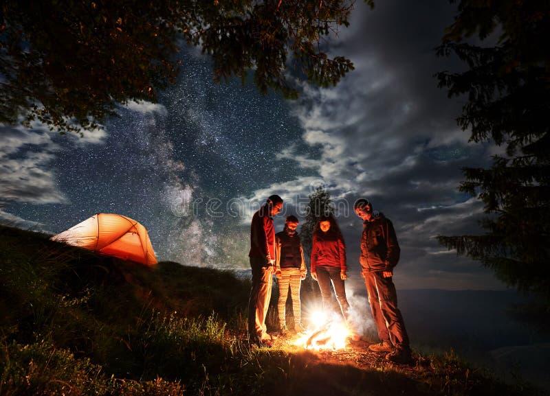 Gruppen av unga turister står runt om branden nära tältet under den molniga himlen med den mjölkaktiga vägen royaltyfri foto
