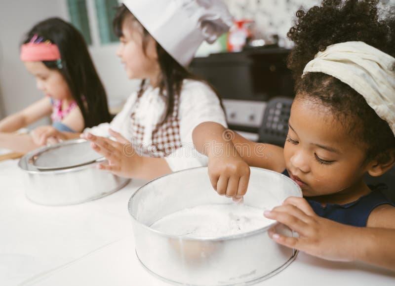 Gruppen av ungar förbereder bagerit i köket Barn som lär till att laga mat kakor fotografering för bildbyråer