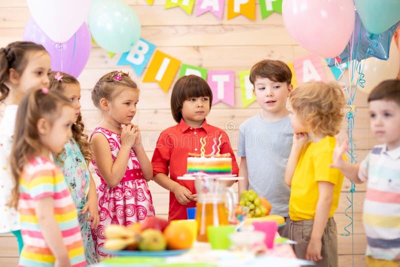 Gruppen av ungar firar f?delsedagpartiet tillsammans royaltyfri foto