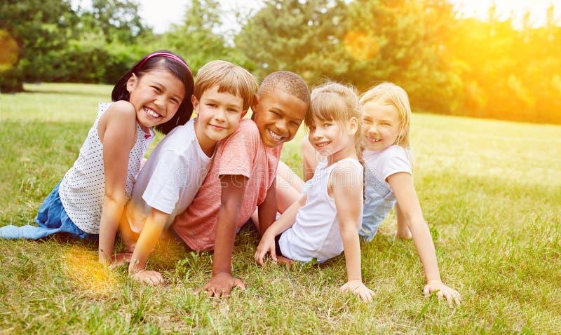 Gruppen av ungar har gyckel i sommar i äng royaltyfria foton