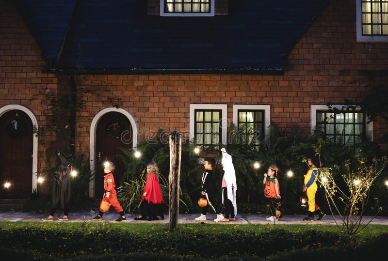 Gruppen av ungar med allhelgonaafton kostymerar att gå till tricket eller behandling arkivfoton