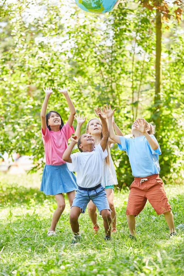 Gruppen av ungar spelar med ett världsjordklot royaltyfri bild