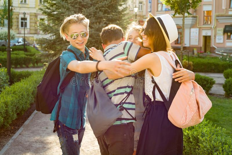 Gruppen av ungdom har gyckel, lyckliga tonåringvänner som går som talar tycka om dag i staden royaltyfria bilder