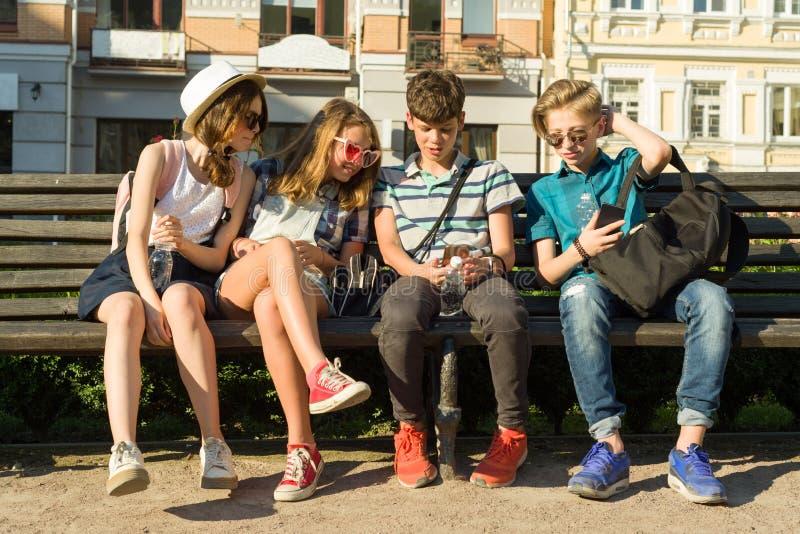 Gruppen av ungdom har gyckel tillsammans utomhus i stads- bakgrund Sommarferier, utbildning, tonårs- begrepp arkivfoto