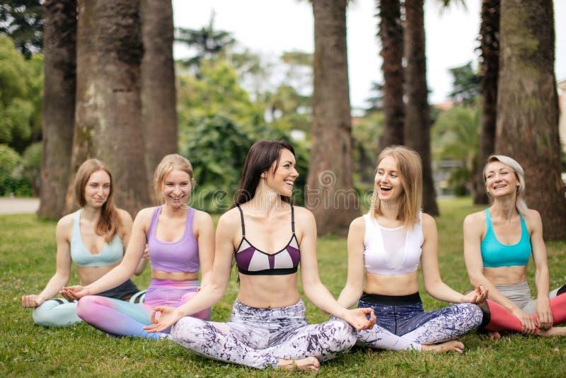 Gruppen av ungdomar har meditation på yoga att klassificera Isolerat på vit arkivbilder