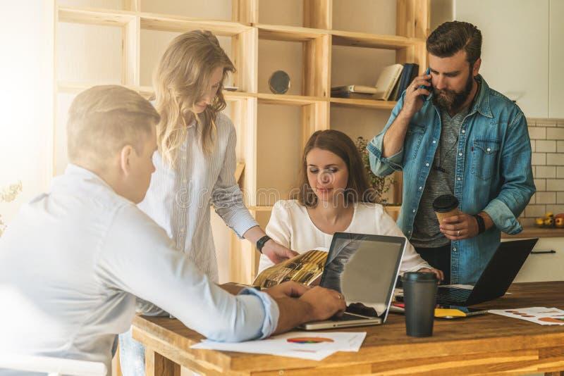 Gruppen av ungdomararbetar tillsammans Mannen använder bärbara datorn, grabb talar på hans mobiltelefon royaltyfri bild