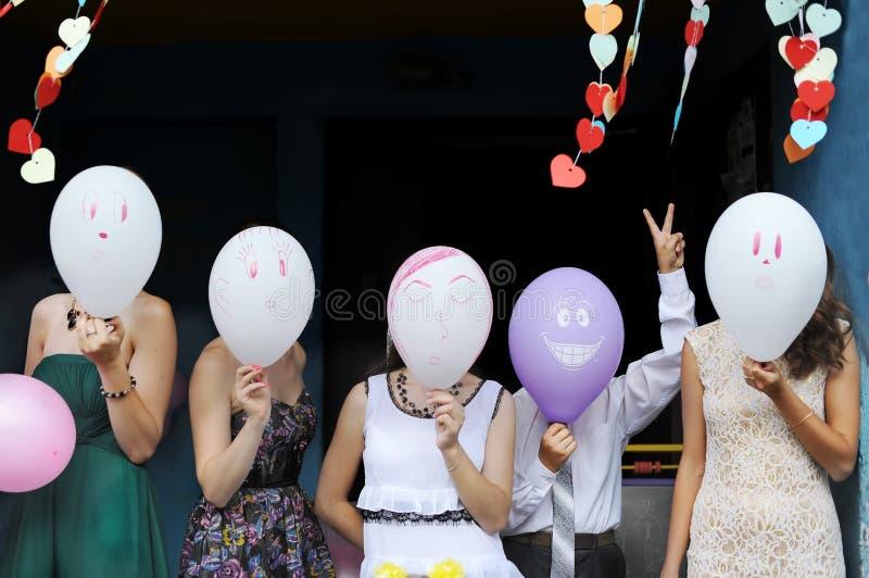 Gruppen av ungdomarhar dolt framsidorna bak ballonger royaltyfria foton