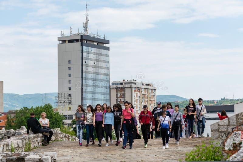 Gruppen av ungdomarmed lopphandbokkvinnan p? en sight turnerar att bes?ka den gamla medeltida f?stningen i staden av Nis, Serbien arkivbilder