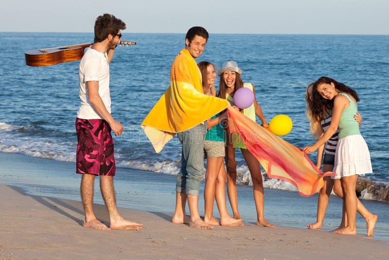 Gruppen av ungdomarsom tycker om stranden, festar med gitarren och ballo royaltyfri bild