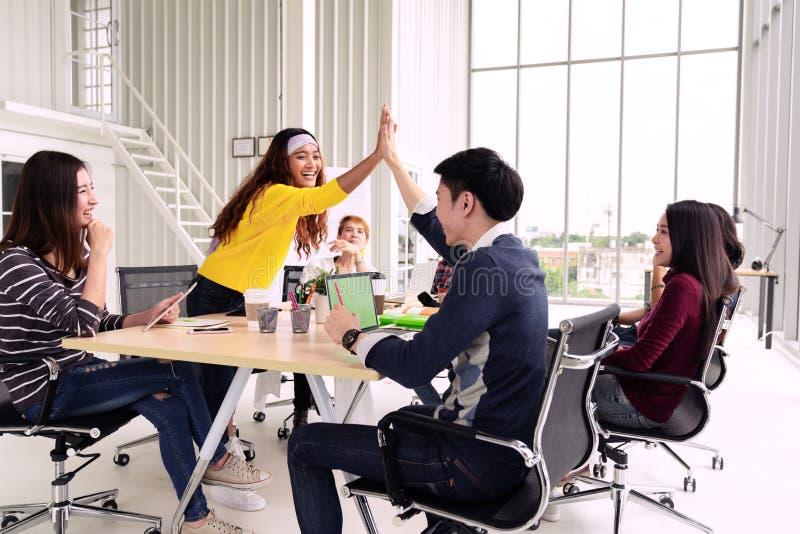Gruppen av ungt multietniskt olikt folk gör en gest hand högt fem och att skratta och le tillsammans i kläckning av ideermöte på  arkivfoto