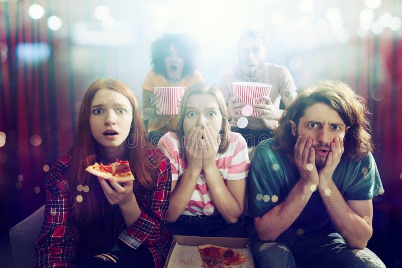 Gruppen av vänner håller ögonen på en film på bion royaltyfri fotografi