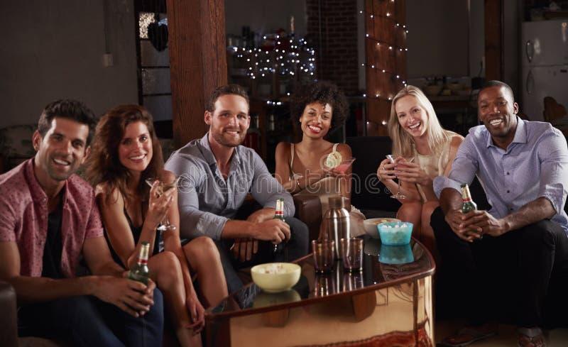 Gruppen av vänner på ett husparti sitter att se till kameran arkivfoto