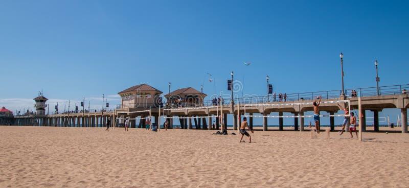 Gruppen av vänner ses att spela volleyboll bredvid Huntington Beachpir arkivfoto