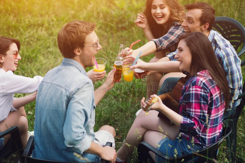 Gruppen av vänner som har picknicken parkerar in royaltyfri bild