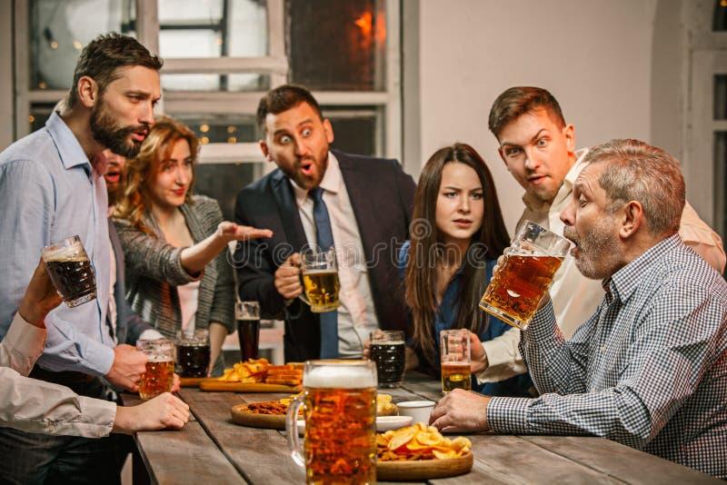Gruppen av vänner som tycker om afton, dricker med öl arkivfoton