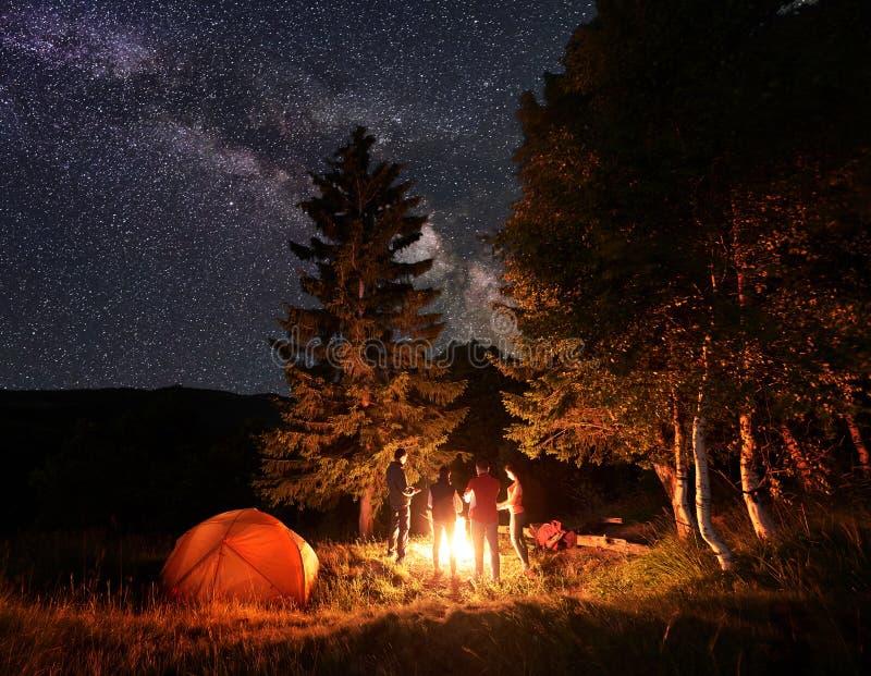 Gruppen av vänner värme deras händer runt om lägereld i trän nära tältet under en ovanligt stjärnklar himmel arkivbilder
