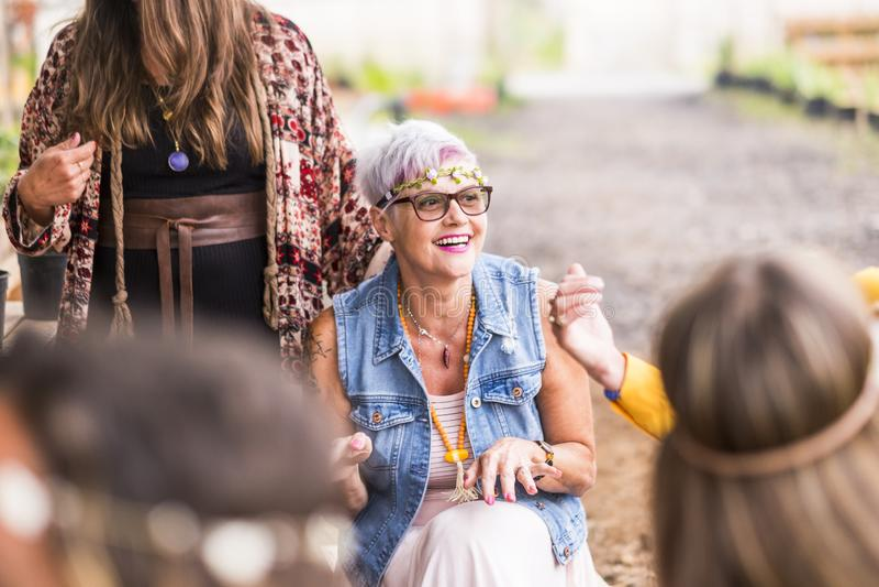 Gruppen av vaggar, och hippy stilkvinnor har gyckel tillsammans i ett parti fira och le begreppet för fria feministiska kvinnlig arkivfoton