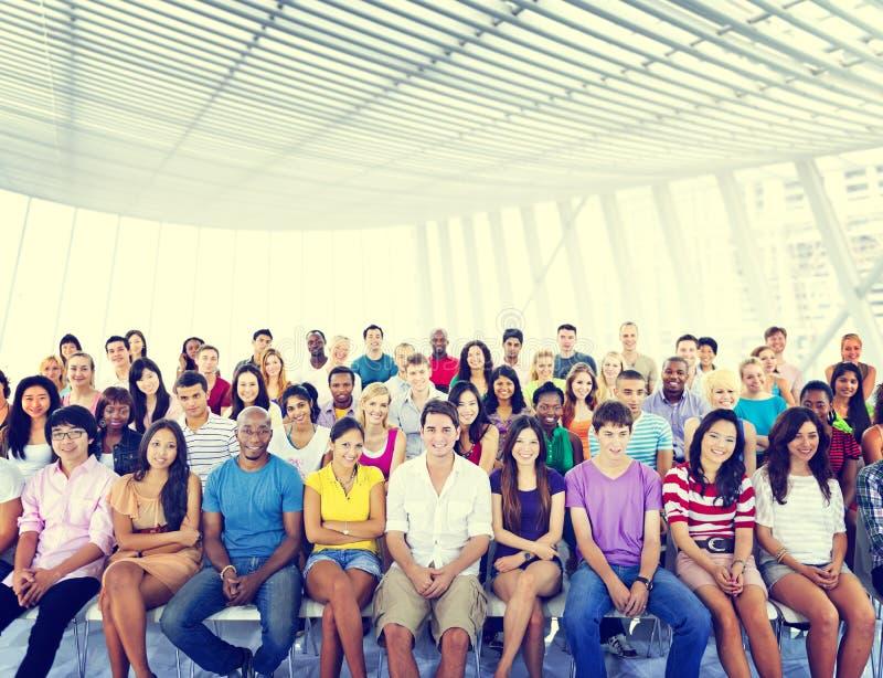 Gruppen-Leute-Mengen-Publikums-zufälliges mehrfarbiges sitzendes Konzept stockfotos