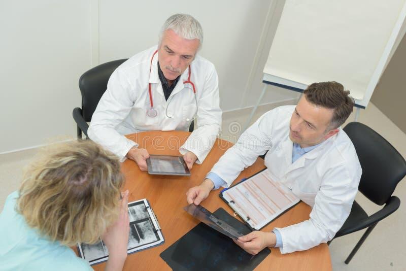 Gruppen manipulerar möte på det medicinska kontoret royaltyfri fotografi