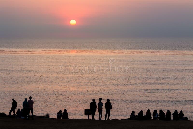 Gruppen Sillhouetted-Leute entlang Klippen watchin sitzen und stehen lizenzfreie stockfotos