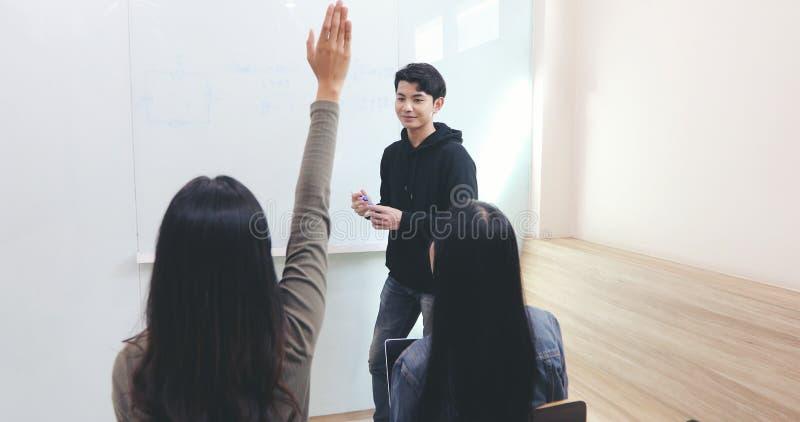 Gruppen-Studenten heben ihre Hände an, um einem Freund Fragen um das Unterrichten am whiteboard im Klassenzimmer zu bitten stockbild