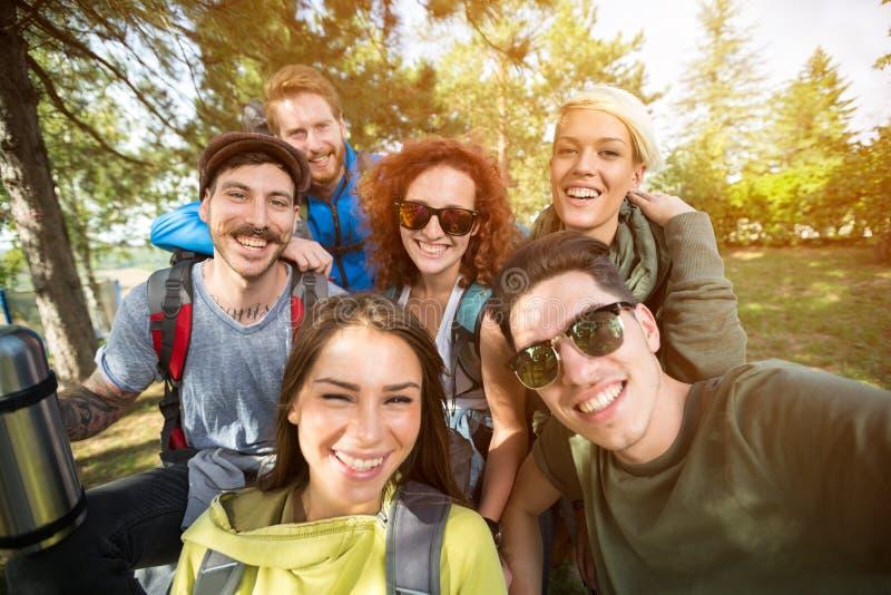 Gruppenfoto von lächelnden Wanderern im Holz lizenzfreie stockfotografie