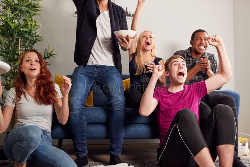 Gruppenfreunde feiern im gemeinsamen Haus beim Spielen im Fernsehen lizenzfreies stockfoto