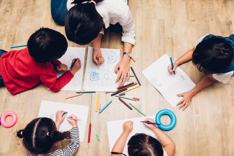 Gruppenkinderjungen- und -mädchenkindergartenfarbenzeichnung Draufsicht Familie glückliche Kinderauf peper Lehrerausbildung lizenzfreies stockbild