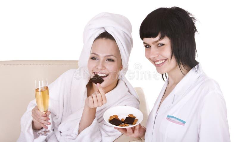 Gruppenmädchen im Badekurort essen Schokolade und trinken Wein. stockfoto