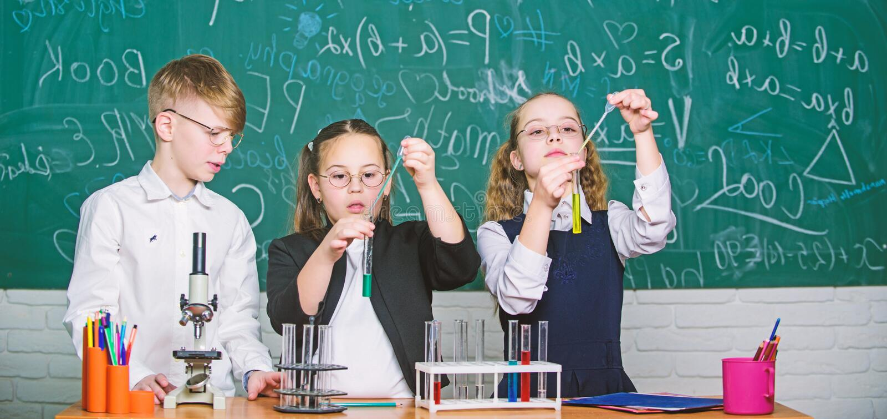 Gruppenschulsch?ler mit Reagenzgl?sern studieren chemische Fl?ssigkeiten Retro- Laborausstattung und B?cher n?hern sich dem Beleu stockbilder