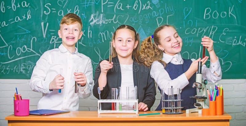 Gruppenschulsch?ler studieren chemische Fl?ssigkeiten M?dchen und Jungenstudentenf?hrungsschulexperiment mit Fl?ssigkeiten Kontro lizenzfreie stockfotos