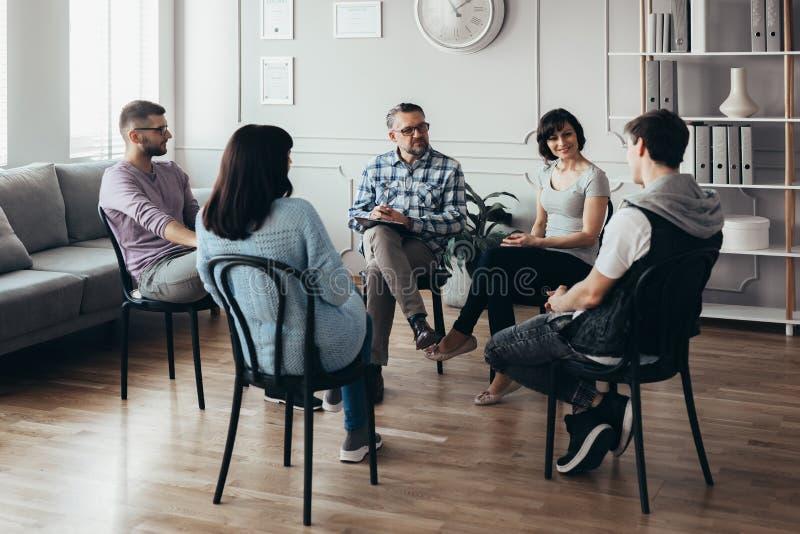 Gruppensitzung für junge Männer und Frauen stockfoto