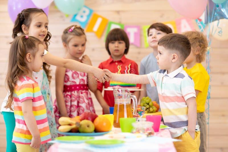 Grupper av barn kommer till partier och skakah?nder med en f?delsedagpojke Ungar har kommit att gratulera deras vän royaltyfri bild