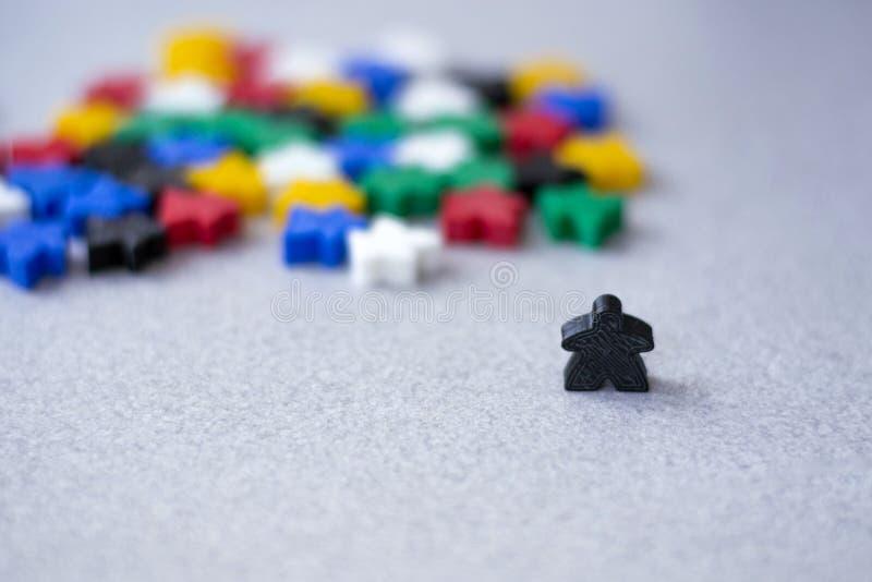 Grupper av färgrika meeples som isoleras på grå bakgrund Små diagram av mannen Begrepp för brädelekar Ledare av folknationen royaltyfri fotografi